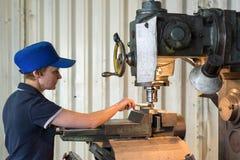 En kvinna på arbete på en vertikal malningmaskin Bearbeta med maskin av en metalldel på enklipp maskin Royaltyfri Bild