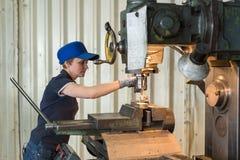 En kvinna på arbete på en vertikal malningmaskin Bearbeta med maskin av en metalldel på enklipp maskin Arkivfoton