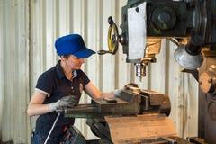 En kvinna på arbete på en vertikal malningmaskin Bearbeta med maskin av en metalldel på enklipp maskin Royaltyfri Fotografi