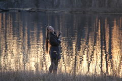 En kvinna på flodbanken i skymningen Arkivbild