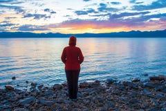 En kvinna på kusten av en stor sjö beundrar solnedgången Fotografering för Bildbyråer