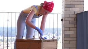 En kvinna p? en terrass g?r ettkvinnlig jobb - borrar ett h?l med en skruvmejsel i en tr?ask stock video