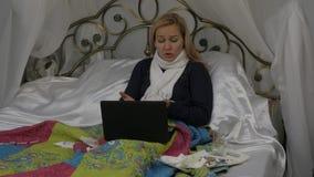 En kvinna plaskar en medicin i näsan nasal spray flickan ligger i en säng med en varm halsduk runt om hans hals 4K stock video