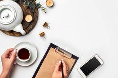 En kvinna räcker handstil på den tomma bokanmärkningen, dagboken, den spridda modellen, den bästa sikten, studio Kopp kaffeavbrot royaltyfria foton