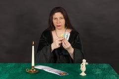 En kvinna är avläsningstarotkort Arkivbild