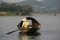 En kvinna ror på en flod i tonen (Vietnam) Arkivfoton