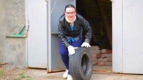 En kvinna rullar ut ett bilgummihjul med en diskett ut ur garaget arkivfilmer