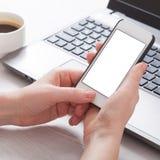 En kvinna rymmer den vita telefonen för smartphonen i arbetsplatsen i rummet Kvinna som använder en mobiltelefon för arbete Arkivfoton