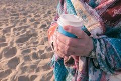 En kvinna rymmer ett exponeringsglas av kaffe arkivbilder