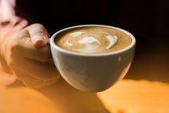 En kvinna rymmer en kopp kaffe royaltyfri foto
