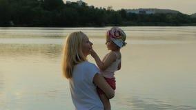 En kvinna rymmer lite flickan i henne armar och kysser henne vid sjön på solnedgångtid arkivfilmer