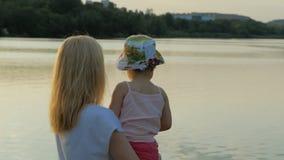 En kvinna rymmer lite flickan vid sjön under solnedgång stock video