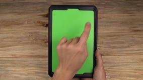 En kvinna rymmer en minnestavlaPC med en grön skärm för ditt eget beställnings- innehåll arkivfilmer