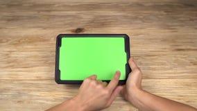 En kvinna rymmer en minnestavlaPC med en grön skärm för ditt eget beställnings- innehåll stock video