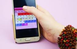 En kvinna rymmer en mobiltelefon med en menstruationkalender royaltyfri fotografi