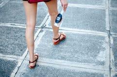En kvinna rymmer en platic flaska med vatten utomhus- Royaltyfri Foto