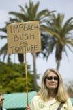 En kvinna rymmer säga för tecken ifrågasätter Bush för tortyr på en marsch för anti--Irak krigprotest i Santa Barbara, Kalifornie royaltyfri fotografi