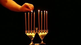 En kvinna rymmer en stearinljus i hennes hand som hon tänder med stearinljus i en Chanukkahlampa