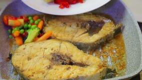 En kvinna sätter nya kulöra grönsaker i en stekpanna med fisken arkivfilmer