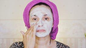 En kvinna sätter på hennes framsida en kosmetisk maskering A stock video