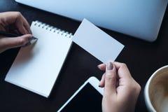 En kvinna` s räcker det hållande tomma vita affärskortet och handstil på den tomma anteckningsboken Royaltyfri Fotografi