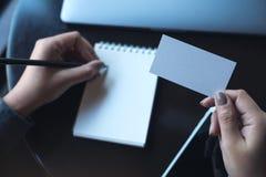 En kvinna` s räcker det hållande tomma vita affärskortet och handstil på den tomma anteckningsboken med bärbara datorn och mobilt Arkivfoto