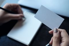 En kvinna` s räcker det hållande tomma vita affärskortet och handstil på den tomma anteckningsboken med bärbara datorn och mobilt Arkivfoton