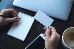 En kvinna` s räcker det hållande tomma vita affärskortet och handstil på den tomma anteckningsboken med bärbara datorn och mobilt Royaltyfri Fotografi