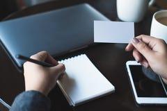 En kvinna` s räcker det hållande tomma vita affärskortet och handstil på den tomma anteckningsboken med bärbara datorn och mobilt Fotografering för Bildbyråer