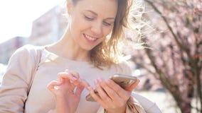 En kvinna ser skärmen av hennes smartphone Flickan skriver SMS och ler medan anseendet i mitt av lager videofilmer