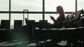 En kvinna sitter i terminalen av den internationella flygplatsen som väntar på hennes flyg Använder en smartphone Arkivbild