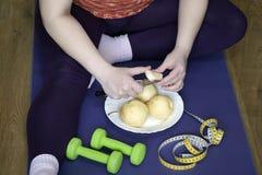 En kvinna sitter på sportar filt och klipper ett päron Royaltyfri Foto