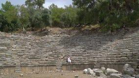 En kvinna sitter på stenmoment i arenan arkivfilmer
