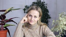 En kvinna sitter på tabellen och ser fast beslutsamt på kameran stock video