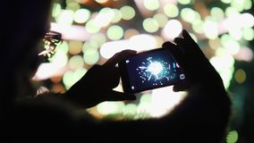 En kvinna skjuter fyrverkerier på en smartphone Ljusen reflekteras beautifully i hennes exponeringsglas Fotografering för Bildbyråer