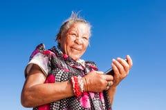 En kvinna som använder hennes nya mobiltelefon Arkivbild