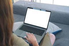 En kvinna som använder och trycker på på bärbar datortouchpad med den tomma vita skärmen, medan sitta i vardagsrum arkivfoton