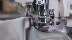 En kvinna som använder en symaskin för att sy tyg tillsammans arkivfilmer