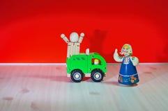 En kvinna som bär en halsduk och en docka som skriker med armar, sträckte ut på en trälastbil Fotografering för Bildbyråer