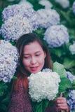 En kvinna som b?r en r?d skjorta i en vanlig hortensiatr?dg?rd fotografering för bildbyråer