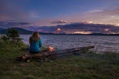 En kvinna som beundrar solnedgången över sjön Arkivbild