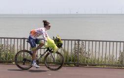 En kvinna som cyklar längs sjösidan royaltyfri bild
