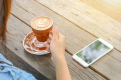 En kvinna som dricker kaffe och använder telefonen på trätabellen arkivbilder