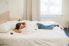 En kvinna som fortfarande som lägger på hennes säng är iklädd hennes kläder till trött som ska fås i sängen Royaltyfria Bilder