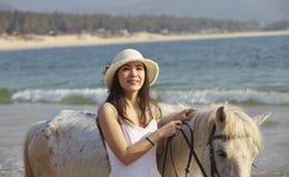 En kvinna som går hästen på stranden Arkivbild