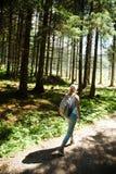 En kvinna som går på skogvägen under sommarkall - håll i form royaltyfri fotografi