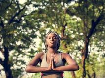 En kvinna som gör yoga i parkera royaltyfri fotografi