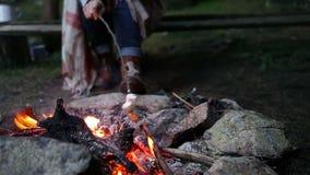 En kvinna som grillar marshmallowen på branden i skogen stock video