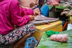 En kvinna som klipper den nya fisken som är till salu i morgonmarknaden arkivbild