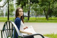 En kvinna som läser en tidning i parkera Arkivfoton